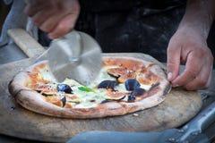 Вырезывание пиццы увольнянной древесиной Стоковые Фотографии RF