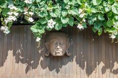 Высекаенная деревянная голова Будды на деревянной стене украшенной с зацветая заводом bali Индонесия стоковая фотография rf