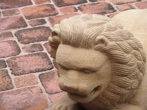 Высекаенный каменный лев на поле кирпича стоковое фото rf