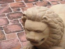 Высекаенный каменный лев на поле кирпича стоковая фотография rf