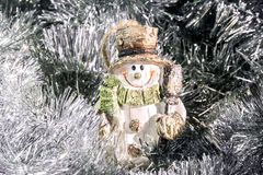 Высекаенный старомодный снеговик между серебряной сусалью Стоковые Изображения RF