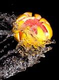 Высеканный грейпфрут в потоке воды стоковые изображения