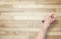 Высекать руки Зубило в руке на деревянной поверхности стоковые фотографии rf