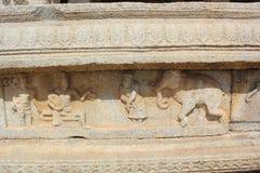 Высекать стены виска Hampi Vittala krishnadevaraya короля и его придворного льстца говоря к торговцу слона Стоковые Фото