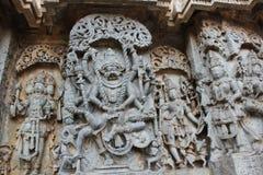 Высекать стены виска Hoysaleswara лорда Narasimha убивая короля демона или злий тиран Hiranyakashyap Стоковые Фотографии RF