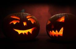 2 высекли стороны тыкв накаляя на хеллоуине на красной предпосылке Стоковое Изображение