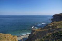 Высокая скала над морем, скала спускает в море, много брызгая волн и камни стоковые фото