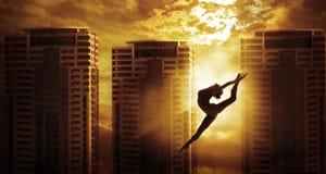 Высокая скачка танцев женщины спорта здания подъема, силуэт танцора Стоковая Фотография