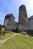 Высокая средневековая башня с каменистыми зданиями вокруг Стоковое Изображение RF