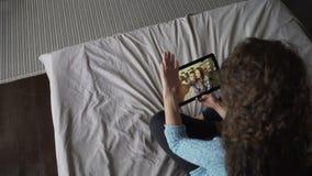 Высокая угловая съемка девушки звоня видео- используя таблетку и говоря к новостям друзей онлайн обсуждая Молодая женщина видеоматериал