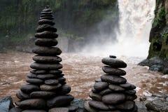 Высокие башни плоской пирамиды из камней камней клали вне на банк на водопаде Традиции буддизма Стоковое Изображение
