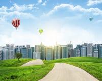 Высокие здания, зеленые холмы и дорога против неба Стоковые Фото