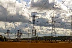 высокие линии приводят напряжение тока в действие стоковые фото