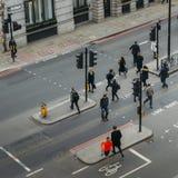 Высокий взгляд перспективы пешеходов работника офицера в городе Лондона пересекая улицу Стоковые Изображения