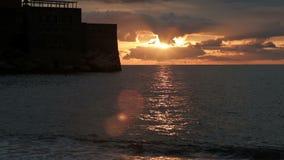 Высокий каменный замок стоит в середине пруда на заходе солнца акции видеоматериалы