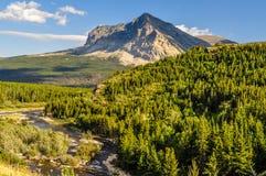 Высокий остроконечный горный пик и пропуская поток в национальном парке ледника стоковое фото rf