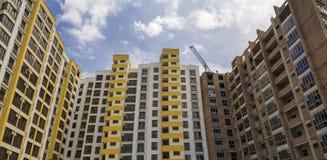 Высокий поднимая многоэтажный жилой кран кирпичного здания и работы квартиры на блоке под конструкцией на предпосылке голубого не стоковое изображение rf