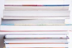 Высокий стог книг изолированный на белой предпосылке стоковые фото