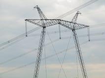 Высоковольтная линия передачи энергии против темного неба Стоковое Изображение