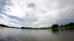 Высоковольтная опора линии электропередач полагаясь над рекой и облака двигают быстро в небо в дневном времени ярком видеоматериал
