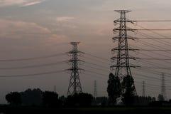 Высоковольтные башни передачи энергии в предпосылке неба захода солнца Стоковое Изображение