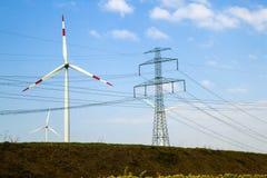 Высоковольтные башня и ветротурбины против голубого неба Стоковые Фото
