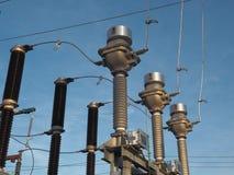 Высоковольтные настоящие трансформаторы и автомат защити цепи на предпосылке голубого неба стоковое фото