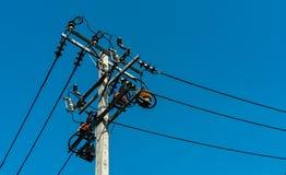 Высоковольтные электрические поляк и передающие линии с ясным голубым небом Опоры электричества в поле ячменя Техническая система стоковое фото