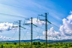 3 высоковольтных башни передачи над облачным небом Стоковые Фотографии RF