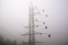 Высоковольтная башня столба на туманной предпосылке раннего утра Стоковые Фото