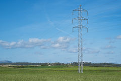 Высоковольтные башня и кабельная линия связи в сельской местности под голубым небом Стоковое фото RF