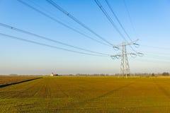 Высоковольтные опора и кабели в плоском ландшафте стоковые фото