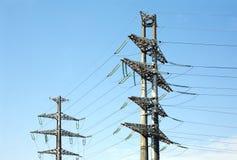 2 высоковольтных упорки металла линии электропередач над голубым небом Стоковая Фотография RF