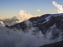 Высокогорные пики в облаках увиденных от хаты Mantova на Monte Роза, Стоковая Фотография