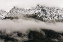 Высокогорные пики затемненные заворотом облака Стоковое Фото