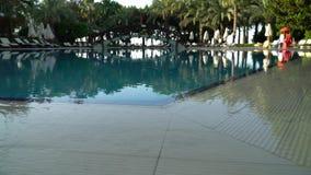 Высокое видео определения - Sunbeds и зонтики вокруг бассейна на гостинице акции видеоматериалы