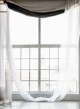 Высокое окно от потолка, который нужно справиться с длинными белыми занавесами Стоковые Изображения