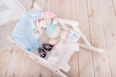 Высокое стульчик с игрушками и одеждами для ребенка Стоковые Фотографии RF