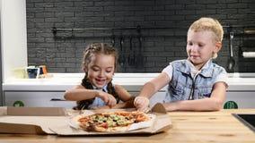 Высококалорийная вредная пища Любимая еда для детей 2 дет есть часть пиццы пробуя первую Концепция образа жизни 4K видеоматериал