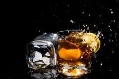 2 высококачественных стекла вискиа, одного лежат на стороне и другое с кусками лимона и льдом и много брызгает Стоковое Фото