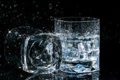 2 высококачественных стекла вискиа, одного лежат на стороне и другое с кубами и водой льда брызгает Стоковые Изображения