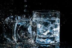 2 высококачественных стекла вискиа, одного лежат на стороне с водой брызгают и другое с кубами льда Стоковая Фотография