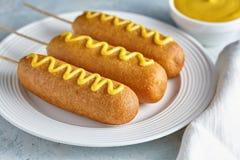 Высококалорийная вредная пища corndog собаки мозоли традиционная американская зажарила закуску сосиски горячей сосиски с мустардо Стоковые Фото