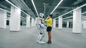 Высокорослый робот приходит к девушке и обнимает ее акции видеоматериалы