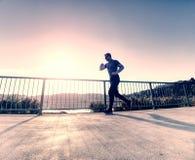 Высокорослый тонкий бег человека на террасе озера против красивого восхода солнца стоковое фото