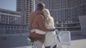 Высокорослый человек обнимает довольно белокурую женщину в теплом положении куртки около велосипеда смотря на высоком здании Бесе сток-видео