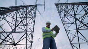 2 высокорослых башни электричества и мужского контролер работая между ими акции видеоматериалы