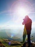 Высокорослый человек принимает фото камерой зеркала на шеи Пик Snowy скалистый горы Стоковые Фото
