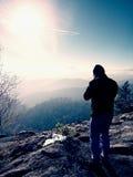 Высокорослый человек принимает фото камерой зеркала на шеи Пик Snowy скалистый горы Стоковое Изображение RF