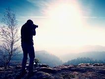 Высокорослый человек принимает фото камерой зеркала на шеи Пик Snowy скалистый горы Стоковое фото RF